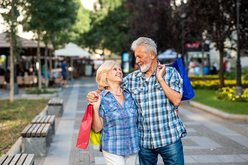 Happy senior couple hugging after shopping in the park. Finding the missing person in your life can change your outlook much like getting a new smile after missing a tooth.