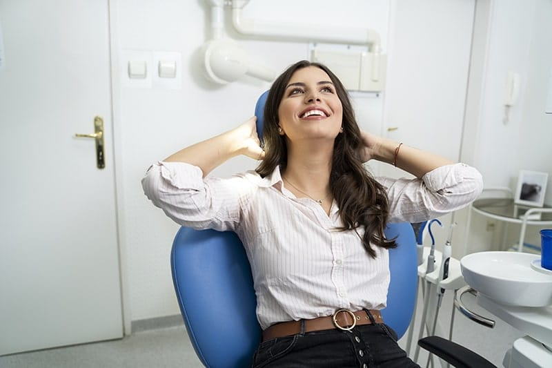 Gorgeous young adult woman keeping calm at her visit at dentist