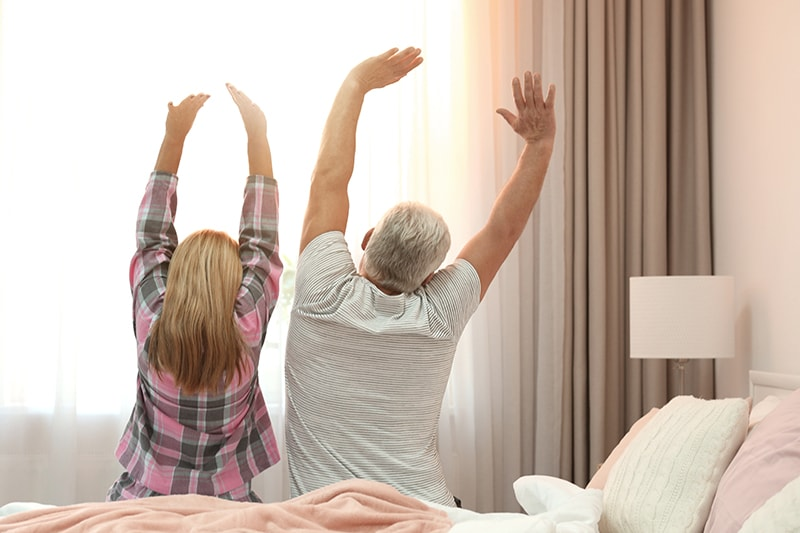 Mature couple stretching on bed after a restful sleep. Managing your sleep apnea will keep you healthy to prevent heart attacks or strokes.