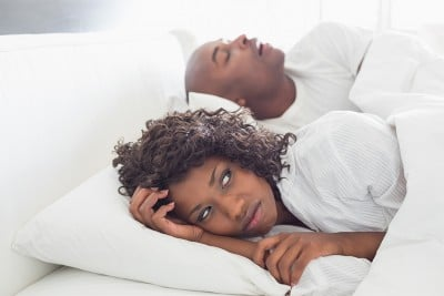 annoyed woman laying next to her snoring husband in bed