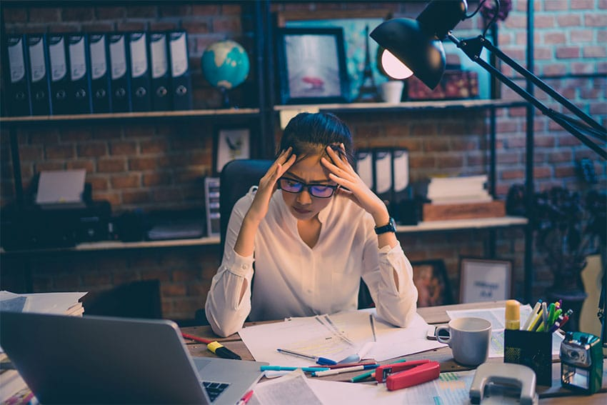 woman sits at her computer stressed out