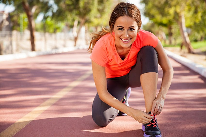 attractive young woman bending down to tie her shoe while running