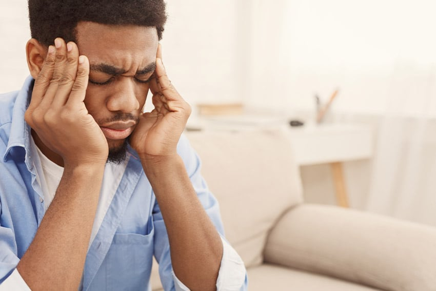 young businessman sitting on his couch with headache