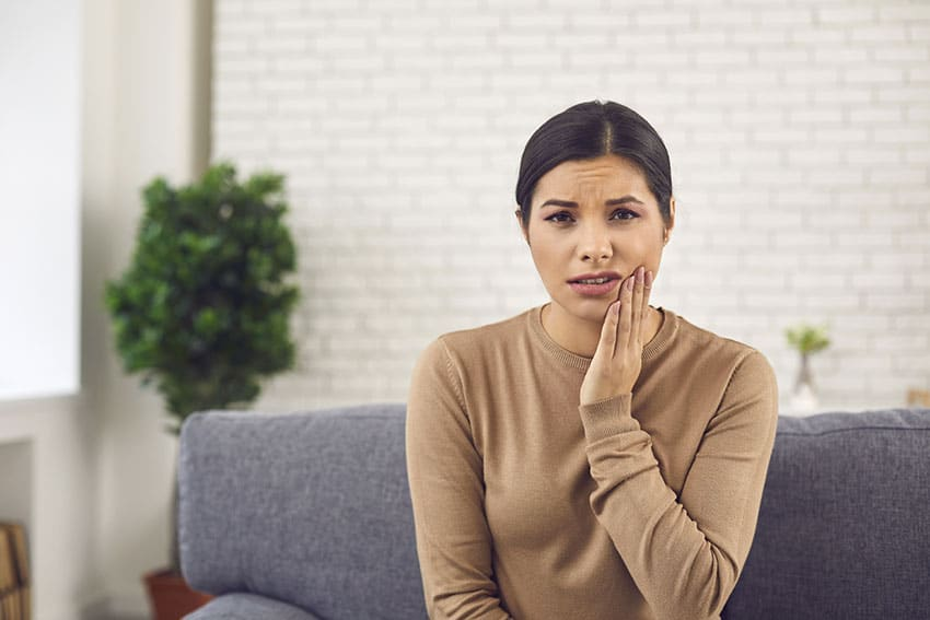 woman sitting on her couch with TMJ, jaw pain
