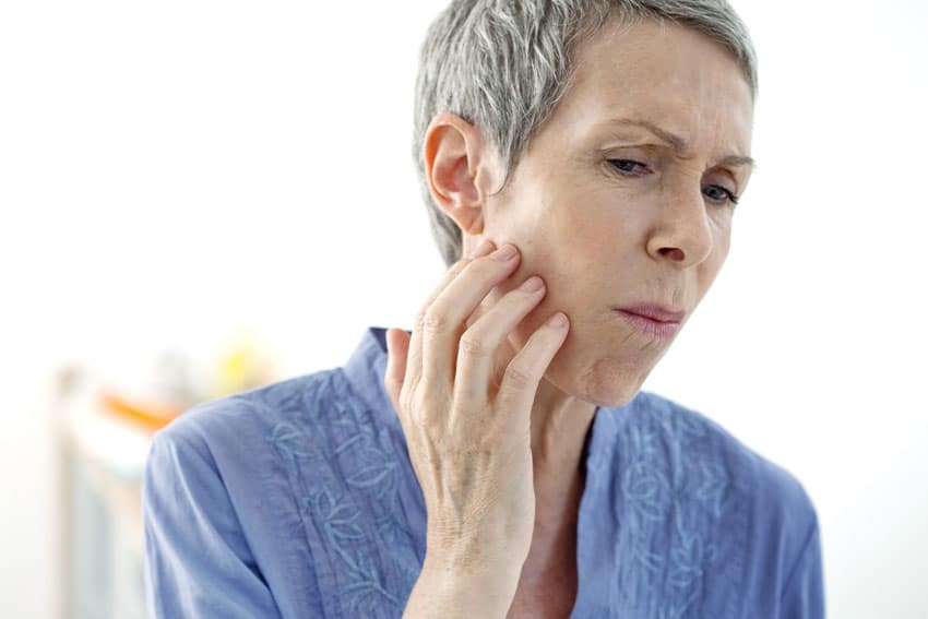 mature woman suffering from TMJ jaw pain